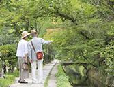 素材辞典 川沿いの遊歩道を歩くシニア夫婦